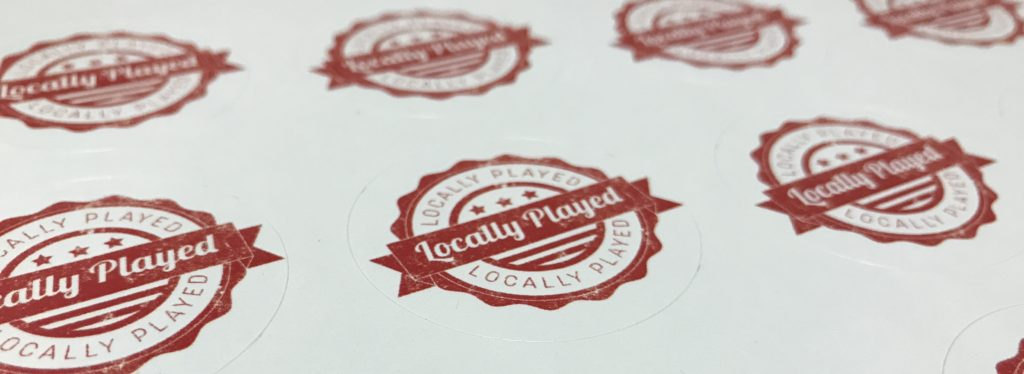 """photograph of stickers saying """"locally played"""""""